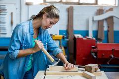 Female carpenter using a hammer Kuvituskuvat