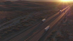 AERIAL: Cars and semi trucks driving on busy highway at summer sunset Stock Footage