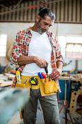 Carpenter removing chisel from tool belt Stock Photos