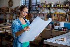 Female carpenter looking at a blueprint Stock Photos