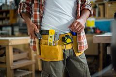 Carpenter removing hammer from tool belt Stock Photos