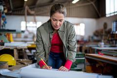 Female carpenter marking on blueprint Stock Photos