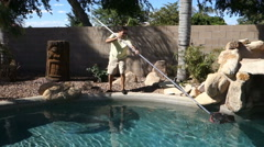 Man Cleans Pool with Skimmer Stock Footage