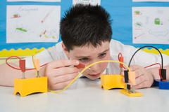 Boy in science lesson - stock photo