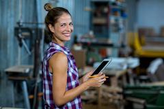Female carpenter using digital tablet Stock Photos