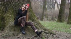 Beautiful young hipster girl sitting by the leafless tree and drinking takeaway Stock Footage