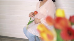 Happy bright pregnant sitting before beige wall, holding tulip. 4k Stock Footage