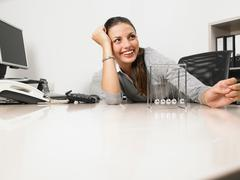 Businesswomen sitting at her desk with a Newton's Cradle Stock Photos