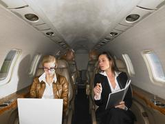 Two women in private jet having a discussion. Stock Photos