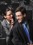 Woman whispering to man sitting in auditorium - stock photo