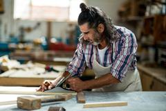 Male carpenter leveling a timber with jack plane Stock Photos