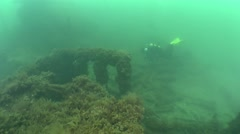 A diver swims against the background of the wreck. Stock Footage