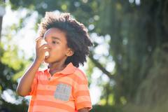 Cute mixed-race boy using a asthmatic spray Stock Photos