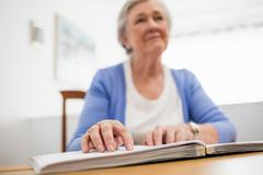 Blind senior woman using braille to read Stock Photos