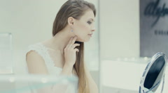 Lovely girl wears jewelry in the bathroom. Stock Footage