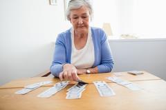 Senior woman playing cards Stock Photos