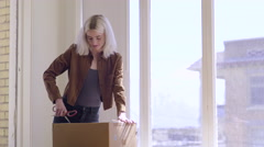 Excited Young Woman Unpacks A Cardboard Moving Box, Opens It With Scissors - stock footage