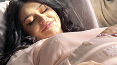 Close up of pregnant woman in nighty reposing and touching her tummy Slowly Stock Footage