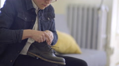 Trendy Man Loosens Boot Laces, Sets Boot Down, Pulls Back On The Heel - stock footage