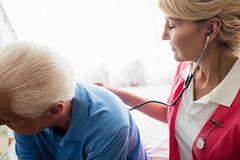 Nurse using stethoscope to take care of a senior man Stock Photos
