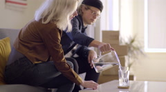 Man Pours Water For His Girlfriend And Himself In Their New Place Stock Footage