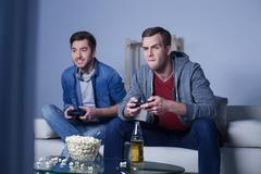 Cheerful two friends are entertaining with play-station - stock photo