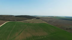 Aerial view of  wheat fields, forest, green landscape, horizon, blue sky, road - stock footage