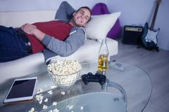 Cute guy is entertaining with modern technology - stock photo