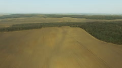 Aerial view of fields, tractor plowing the soil in spring day, near the forest Stock Footage