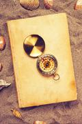 Vintage book and compass on sandy beach - stock photo