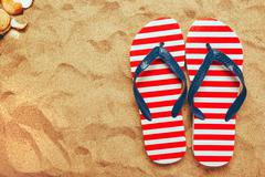 Pair of thongs or flip flops on beach sand - stock photo