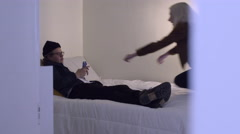Man Looks Bored, Plays On His Phone, His Girlfriend Jumps On Him, They Cuddle Stock Footage