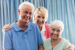 Nurse hugging a senior couple Stock Photos