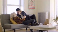 Couple Carry A Load Of Stuff Into New Apartment, Then Collapse On The Couch Stock Footage