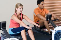 Woman and man on rowing machines Stock Photos