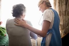 Nurse taking care of a senior woman Stock Photos