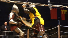Two medieval knight fighting in an arena with swords and shields. Slow motion. - stock footage