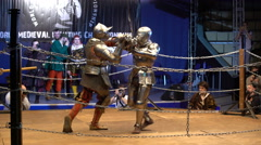 Two medieval knight fighting in the arena two-handed swords. - stock footage