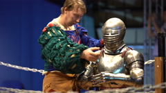 A squire helps a knight to wear a helmet before a fight. - stock footage