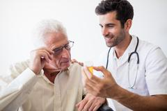 Nurse giving pills to senior man Stock Photos