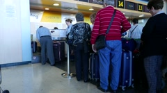 Airline passengers checking in at a counter in the Valencia, Spain Airport. Stock Footage