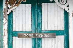 Gone fishing sign at weathered doors - stock photo