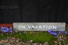 On vacation sign by blue flowers - stock photo