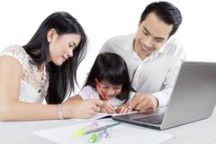 Asian parents teach their child to write - stock photo