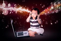 Baby boy listening music - stock photo