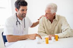 Nurse giving medicine to senior man Stock Photos