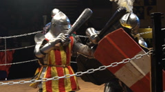 Two medieval knights fighting in the arena with clubs and shields. Slow motion. - stock footage