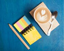 Hot drink with notebook on the table Stock Photos