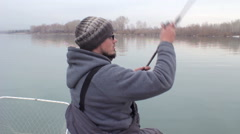 Mid-aged man casting off a dock and fishing alone on an overcast day. Stock Footage