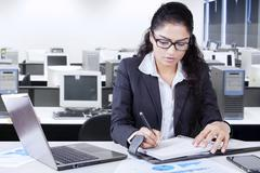 Worker writes a journal in office - stock photo